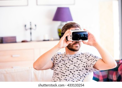 Man wearing virtual reality goggles, sitting in living room