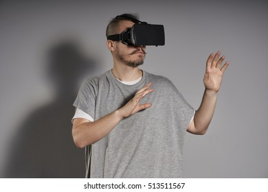 Man wearing virtual reality goggles. gray background