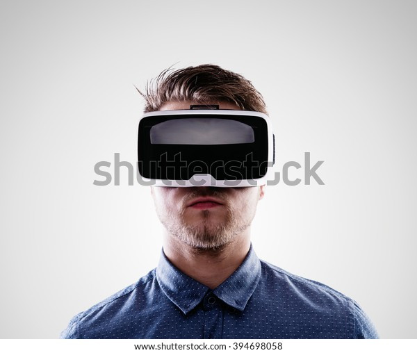 Man wearing virtual reality goggles. Studio shot, gray backgroun