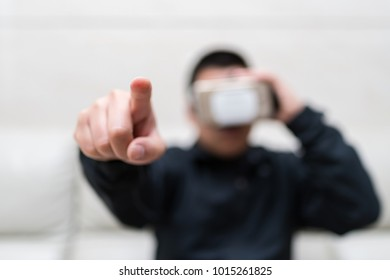 man wearing VR Glasses or Virtual Reality headset with his finger feeling the simulation world selective focus