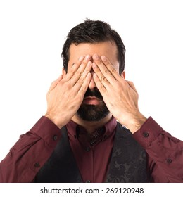 Man wearing waistcoat covering his eyes