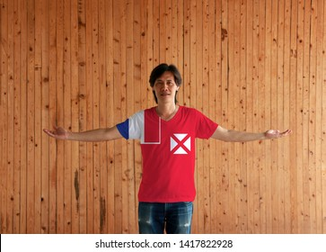 Man wearing Wallis and Futuna flag color shirt and standing with arms wide open on the wooden wall background, red saltire on a white square, the flag of France in the upper.