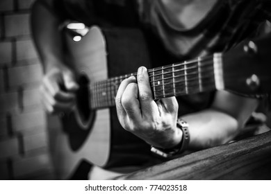 Man wearing watch is playing acoustic guitar in the red bricks background room. , black and white style.
