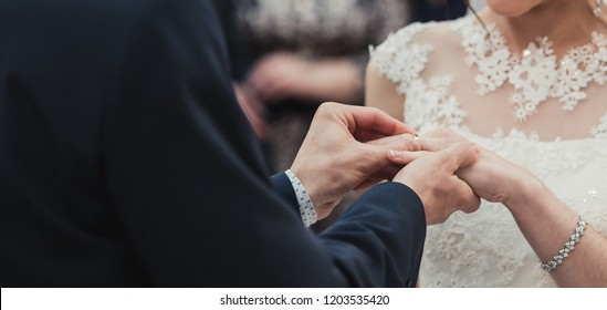 a man wearing a wedding ring for his bride during the ceremony and the sacrament of the wedding. A pair of pairs