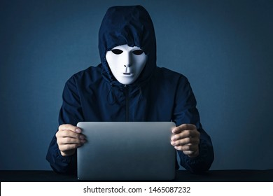 Man wearing a white mask with a personal computer