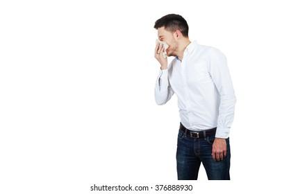 Man wearing white shirt blows his nose