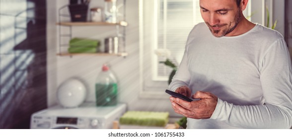 Man wearing white shirt using smart phone while ironing clothes in laundry room at home