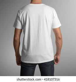 Man wearing white t-shirt, back view, isolated on gray background, with clipping path to change background