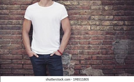 man wearing white t-shirt on brick wall background