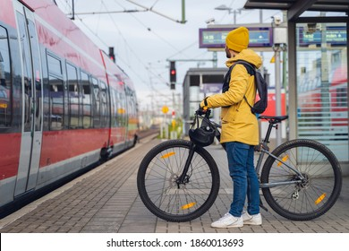 A man, wearing winter clothes, at the station, is about to get on the train, with his bicycle.