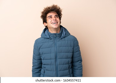 Man wearing winter jacket over isolated background looking up while smiling