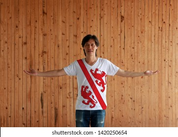 Man wearing Winterthur flag color shirt and standing with arms wide open on the wooden wall background. The canton of Switzerland Confederation.