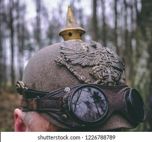 A man wearing World war 1 german  spiked helmet (Pickelhaube) and dust glasses on a historical reenactment event