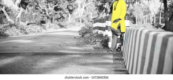 Man wearing yellow punjabi dress standing beside a road