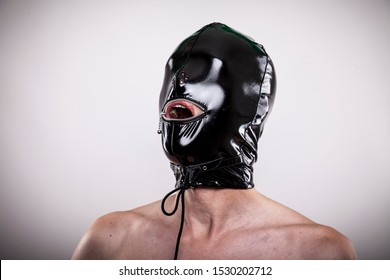 man wears black shiny smooth glossy latex mask on his head. portrait isolated against white background. expressing dominance and submission.