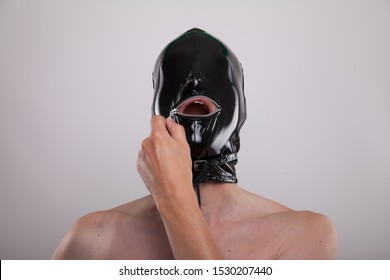 man wears black shiny smooth glossy latex mask on his head. portrait isolated against white background. expressing dominance and submission. opening mouth zipper with hand