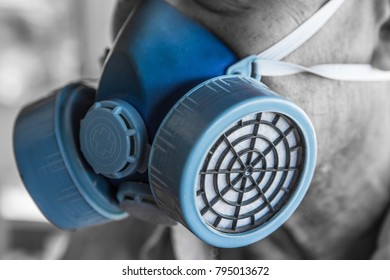 Man wears a blue chemical mask close up