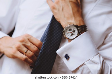 The man wears a blue tie,a watch on his arm. A close-up photograph
