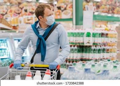 Man wears disposable medical mask and rubber gloves, stands in supermarket with trolley, makes shopping, buys necessary products during quarantine. Protection and prevent measure while epidemic time