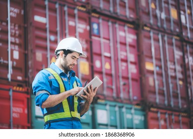 Man wears hardhat and reflection shirt and checking tablet with blurry metal containers in background. Concept of inventory and logistic management.