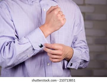 The man wears a shirt with cufflinks