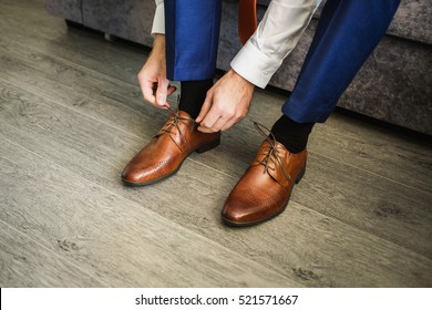 The man wears shoes. Tie the laces on the shoes. Men's style. Professions. To prepare for work, to the meeting.