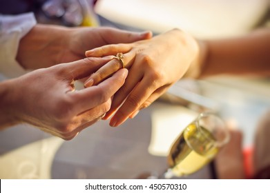 The man wears a wedding ring on woman's hand