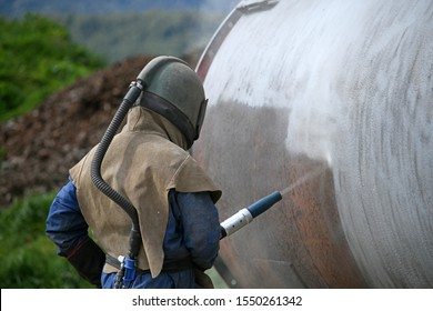 A man weating full safety gear uses ground glass to sandblast the steel casing of a meat drying machine for a rendering plant