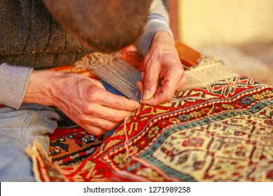 man weaving carpet