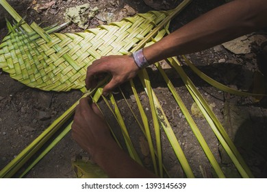 A man is weaving palm for Palm Sunday. Typical Venezuelan tradition, people go to the mountains to fetch the royal palm and give it to churches for Palm Sunday