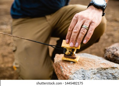 Man with wedding band making a s'more while camping.
