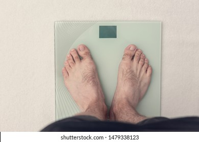 Man is weighed on scales, men's legs, closeup, top view