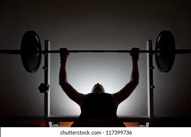 Man weightlifter at the gym, lifting weights on a benchpress