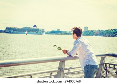 Man Welcomes You. Wearing white shirt, holding white rose, a guy standing by Hudson River in New York, opposite New Jersey, looking faraway. Boat, cruiser on background. Instagram effect. Copy Space.