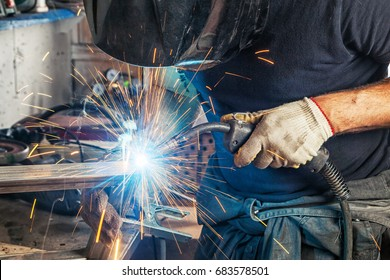 A man welder in a black T-shirt, construction gloves and a welding mask hard work and  welds with a welding machine metal in workshop, close up