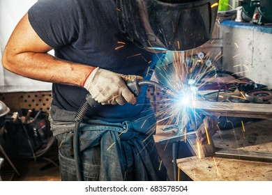 A man welder in a black T-shirt, construction gloves and a welding mask hard work and  welds with a welding machine metal in workshop