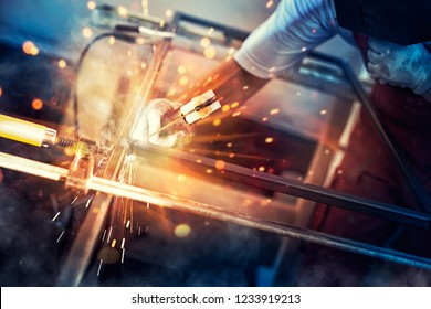 A man welder with construction gloves and a welding mask is enthusiastically working and is welded with a welding machine metal in workshop