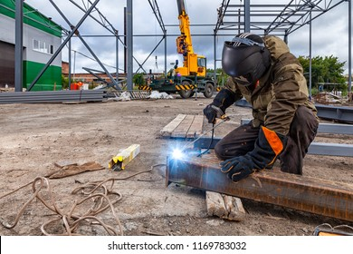 Man welder in welding mask, building uniform and blue protective gloves brews metal welding machine on street construction, in the background construction site