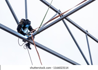 A man  welder working at height with insurance  in  welding mask is weld metal and is sitting on a metal structure at an altitude against the blue sky