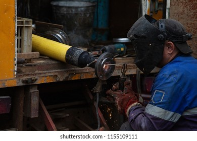 a man in a welder's mask and in a robe works in the factory, is engaged in welding work, the flow of hot plasma welds the seam on a metal pipe, production, plant and rough work