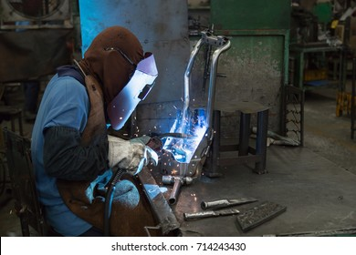 Man is welding an automotive part.