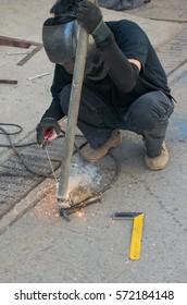 Man with welding helmet welding steel