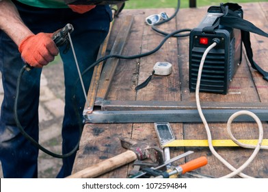 a man welds a metal with a welding machine, profession of welder, weld metal, man works with metal