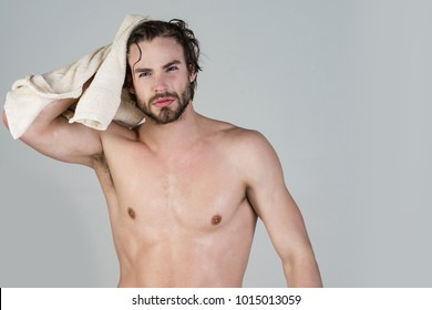 Man with wet hair hold towel after shower. Morning washing, wake up, everyday life. Refreshment, healthcare. Hygiene, sexy guy wash, spa, relax. Man in bathroom with muscular body on grey background.