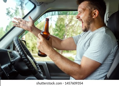 A man at the wheel holds a bottle of alcohol in his hand while driving, violates traffic rules. The concept of an accident, a traffic violation.