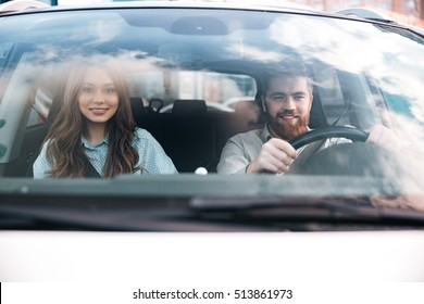 Man at the wheel with woman in car. front view. smiling couple
