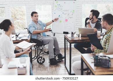 A man in a wheelchair demonstrates business graphics. He is holding a green marker. Collegues are listening attentively to him.