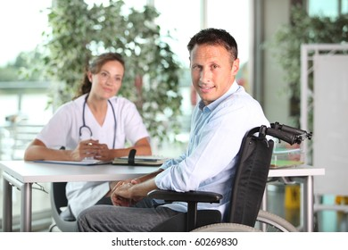 Man in wheelchair with doctor in hospital