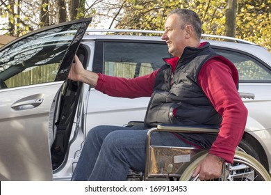 Man in a wheelchair in the fall next to their car