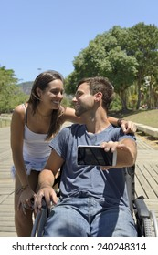 Man in wheelchair and girlfriend taking a selfie with smartphone